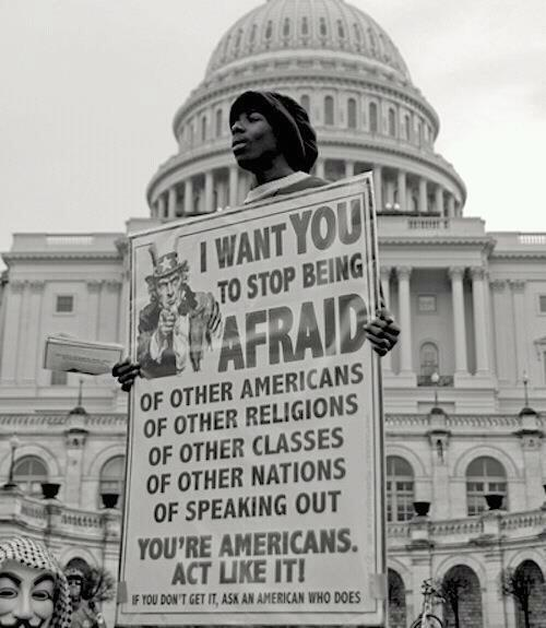 """Washington DC: A black man holds a poster with Uncle Sam on it that says I want you to stop being afraid of other americans, of other religions, of other classes, of other nations, of speaking out. You're Americans. Act like it! If you don't get it, ask an American that does. The bottom left corner also has the head of a person wearing a Guy Fawkes mask barely visible. Source unknown."""